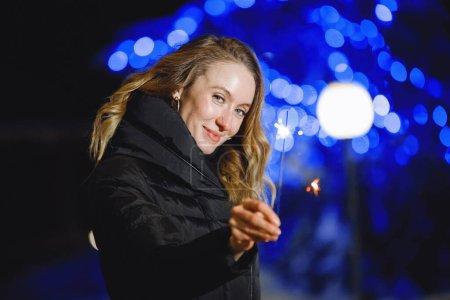 Photo pour Femme avec étincelant dans une veste en duvet à l'extérieur en hiver sur le fond d'un arbre de Noël avec une guirlande bleue. Concentration sélectionnée, lumières floues. Filtre pour bruit et grain. - image libre de droit