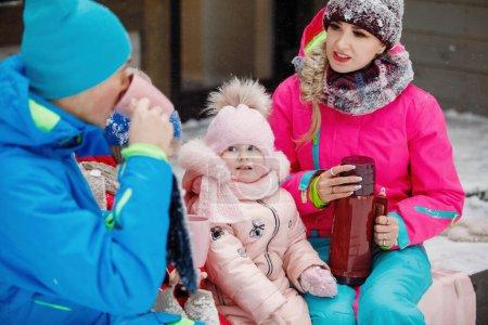 Photo pour Famille - mère, père et fille en hiver près de la maison verser le thé chaud d'un thermos dans une tasse à l'extérieur . - image libre de droit