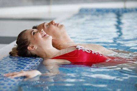Photo pour Jeune couple mignon, Homme et femme loisirs dans la piscine. Elle est en maillot de bain rouge, eau bleue. Concentration sélective. Flou de fond . - image libre de droit