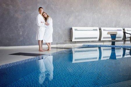 Photo pour Deux se tiennent près de la piscine dans le spa. Un homme et une femme en peignoirs blancs, pieds nus, étreints près de l'eau bleue . - image libre de droit