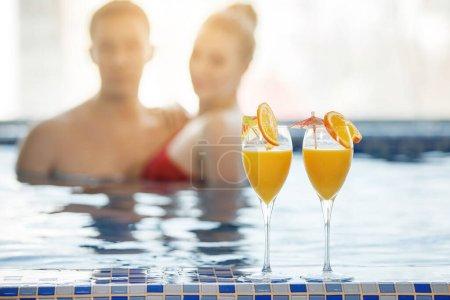 Photo pour Deux verres de jus d'orange avec des tranches sur le fond d'un couple dans la piscine. Une femme et un homme nagent dans l'eau bleue. Concentration sélective. Fond flou . - image libre de droit