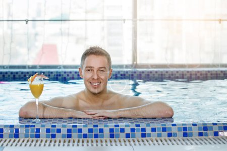 Photo for Man with a glass of orange juice on the side of the pool is looking at the camera. Selective focus. Blur background. - Royalty Free Image