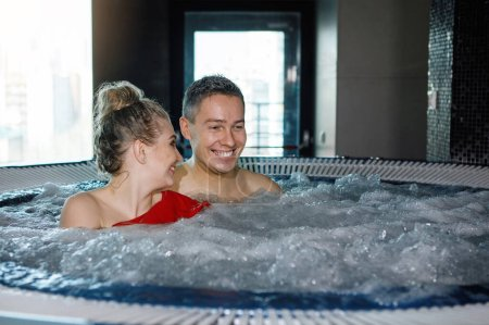 Photo for Young, pretty couple is relaxing in the jacuzzi. Blue foamy water, happy smiles, togetherness. Selective focus, blurred background. - Royalty Free Image