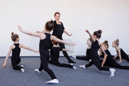 Photo pour Les filles font la division gymnastique sous la direction d'un entraîneur dans l'entraînement de danse. Justaucorps noir, cheveux dans un chignon, chaussettes blanches. - image libre de droit