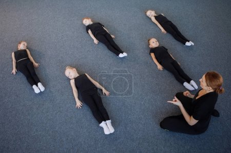 Photo for Gymnastics trainer conducts leg stretching exercises for girls in training. Black leotard, hair in a bun, white socks. - Royalty Free Image