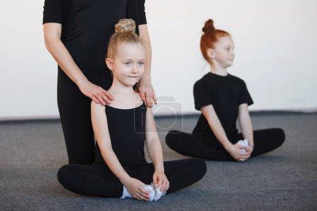Photo pour Deux danseuses sont assises sur le sol en position lotus dans des cours de ballet. Focus sélectionné. Justaucorps noirs, cheveux en chignon, chorégraphie, attention, chaussettes blanches. - image libre de droit