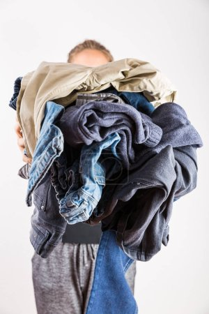 Photo for Woman holding huge pile of clothes - laundry concept - Royalty Free Image