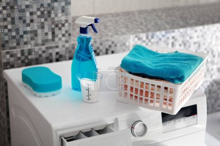 Part of washing machine and blue laundry powder fo...