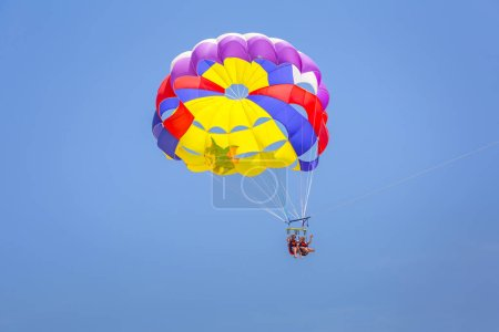 Side, Turkey - June 12, 2018: Tourist on parasailing over the turkish riviera near Side, Turkey. Parasailing is a popular summer activity where people are towed behind a boat at the sea.