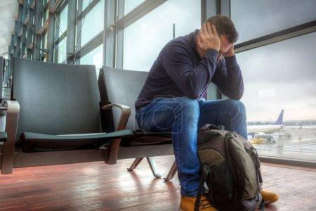 Photo pour Homme déprimé, attendant le départ de l'avion retardé - image libre de droit