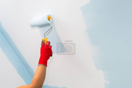 Painter hand painting a wall with paint roller
