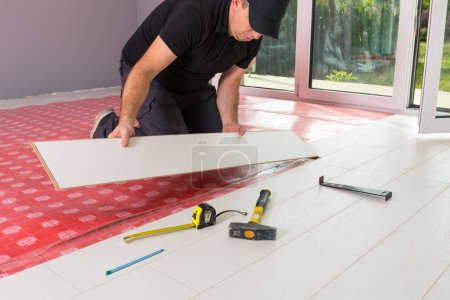 Photo pour Handyman installation de nouveau plancher en bois stratifié - image libre de droit