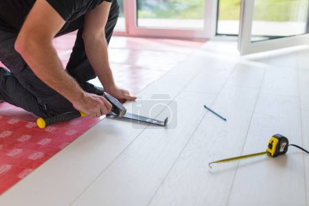 Photo for Handyman installing new laminated wooden floor - Royalty Free Image