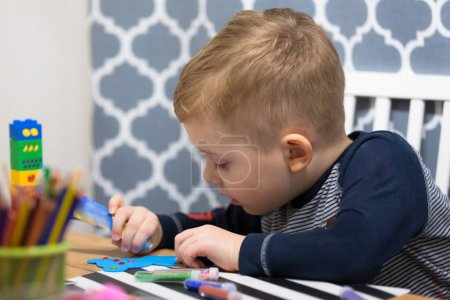 Photo for Cute little boy doing preschool homework and painting. - Royalty Free Image