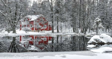 house with water reflection in river in winter, Sweden