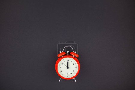 Concept image of a red vintage alarm clock with twelve o clock on dark black color paper background with copy space in minimal style, template for text