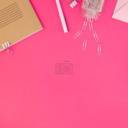 Top view flat lay of workspace desk styled design office supplies with copy space on a bright pink color paper background minimal style. Square Template for feminine blog social media