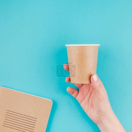 Photo for Creative flat lay of woman hand holding craft paper coffee cup and notebook diary with copy space on turquoise background in minimalism style. Square Template for feminine blog, social media - Royalty Free Image