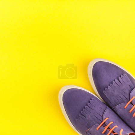 Flat lay of stylish suede shoes on bold yellow paper background with copy space. Overhead view of woman casual outfit. Square hipster look top view
