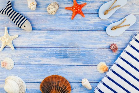 Photo for Creative flat lay concept of summer travel vacations. Top view of towel flip flops seashells and starfish on pastel blue wooden planks background with copy space in rustic style frame template text - Royalty Free Image