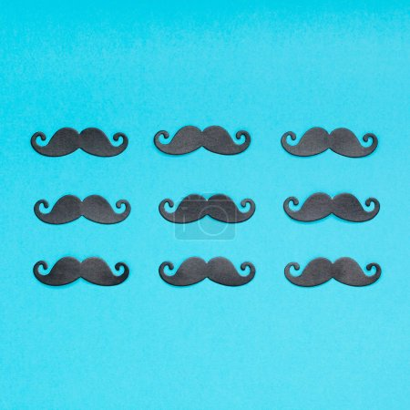 Creative square flatlay overhead top view retro stylish black paper moustaches turquoise background copy space. Men health awareness month fathers day masculinity concept blog social media
