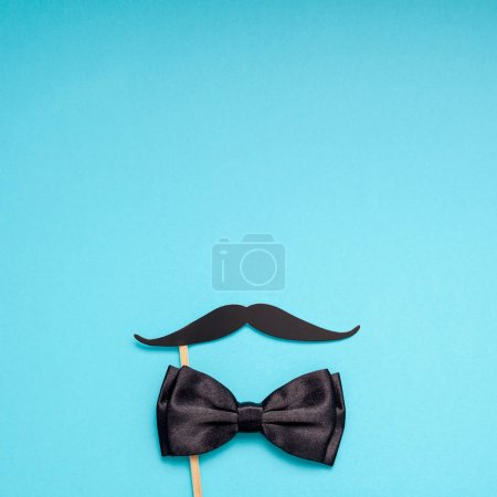 Creative square flatlay overhead top view retro black paper photo booth props moustaches turquoise background copy space. Men health awareness month fathers day masculinity concept blog social media