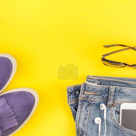 Photo pour Pose plate de chaussures en daim, jeans bleus, chapeau gris, casque cactus et smartphone sur fond papier jaune audacieux avec espace de copie. Vue aérienne de la tenue décontractée femme. Hipster carré look vue de dessus - image libre de droit