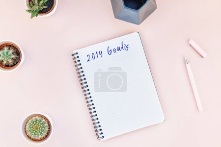 Photo for Top view flat lay of workspace desk styled design office supplies and cactuses 2019 Goals resolutions with copy space millennial pink color background minimal style Template feminine blog social media - Royalty Free Image