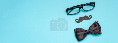 Creative long wide banner top view retro stylish black paper photo booth props moustaches turquoise background copy space. Men health awareness month fathers day masculinity concept blog social media