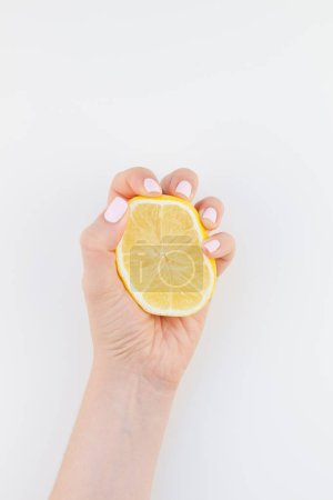 Photo for Woman hand with pastel manicure polish holding a half of lemon isolated on white background copy space minimalism style. Template for feminine social media. Healthy eating concept - Royalty Free Image