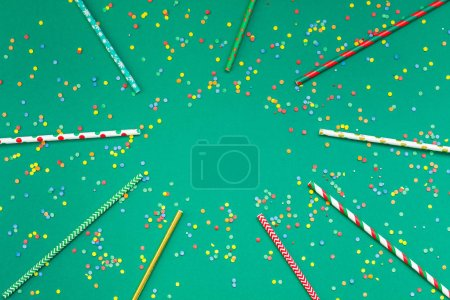 Photo for New Year or Christmas pattern 2019 flat lay top view Xmas holiday celebration drinking cocktail party straws green paper colorful confetti background. Template for greeting card your text design - Royalty Free Image