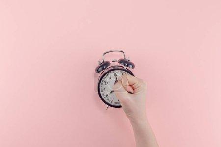 Photo pour Créatif plat matin temps émotions concept vue du dessus de la main femme tenant noir vintage réveil pastel millénaire couleur rose fond de papier avec espace de copie modèle de style minimal pour le texte - image libre de droit