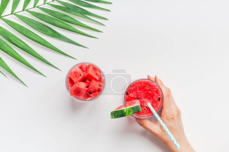 Photo for Creative scandinavian style flat lay top view of fresh watermelon slices smoothie drink in glass woman hands on white table background copy space. Minimal summer fruits concept for blog or recipe book - Royalty Free Image