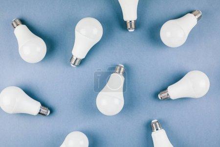 Photo pour Vie économe en énergie et respectueuse de l'environnement dans le modèle de cadre conceptuel. Vue de dessus créative à plat de composition d'ampoules LED avec espace de copie sur fond bleu dans un style minimal . - image libre de droit
