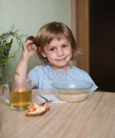 Photo pour Petite fille assise dans la cuisine et mangeant des flocons d'avoine . - image libre de droit