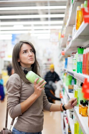 Photo for Young woman choosing   skin care product in   store. - Royalty Free Image