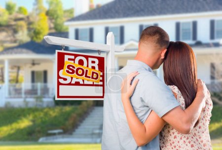 Military Couple Looking At House with Sold For Sale Real Estate Sign In Front.
