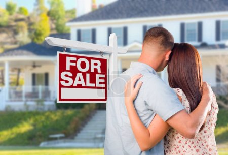 Military Couple Looking At House with For Sale Real Estate Sign In Front.