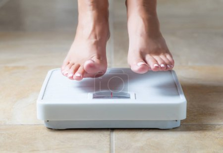 Woman Floating Slightly Above Sruface of Weight Scale.