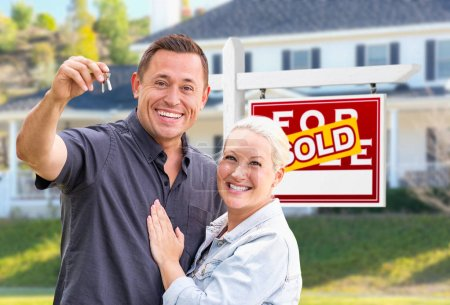 Young Adult Couple With House Keys In Front of Home and Sold For Sale Real Estate Sign.