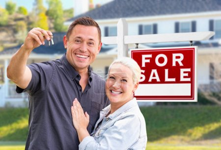 Young Adult Couple With House Keys In Front of Home and For Sale Real Estate Sign.