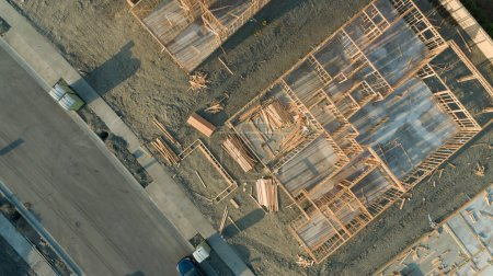 Drone Aerial View of Home Construction Site Foundations and Framing.