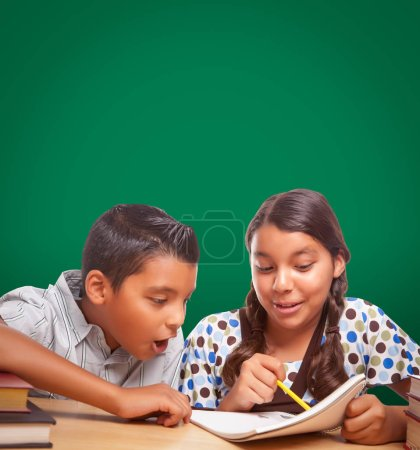 Photo for Blank Chalk Board Behind Hispanic Boy and Girl Having Fun Studying Together. - Royalty Free Image