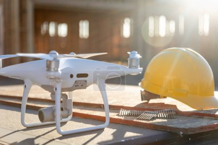 Drone Quadcopter Next to Hard Hat Helmet At Construction Site.