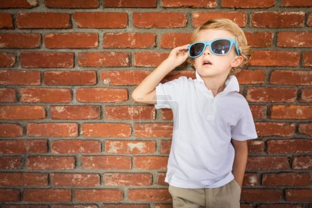 Cute Young Caucasian Boy Wearing Sunglasses Against Brick Wall.