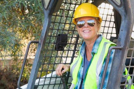 Photo pour Travailleuse souriante utilisant un petit bulldozer sur le site de la constriction - image libre de droit