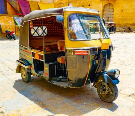 Traditional back and yellow motorized rickshaw in a Jaisalmer square, Rajasthan, India