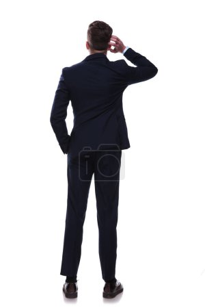 rear view of businessman scratching his head and thinking while standing on white background