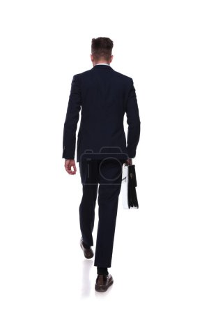 back view of stepping businessman in navy suit with briefcase in hand on white background, full body picture