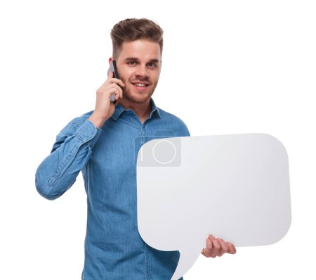 portrait of young casual man with speech bubble speaking on the phone while standing on white background